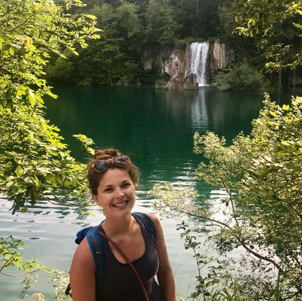 Kelsey Furman standing in front of a lake with a waterfall in the background