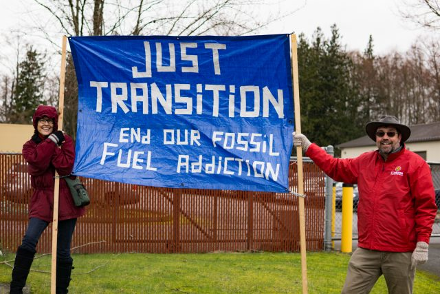 """Two people holding a sign that says """"Just Transition: End Our Fossil Fuel Addiction"""" at an appeal hearing against Tesoro."""